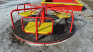 Stock Video Footage of triple baby spinning carousel yellow chairs red rails