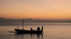 Fisherman in Bali at sunrise on his Jukung Stock Footage