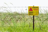 Razor wire guard fence and warning sign on mines field Stock Photos