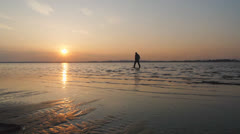 Man walking along the beach at sunset Stock Footage