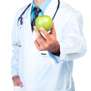doctor's hand holding a fresh green apple close-up - stock photo
