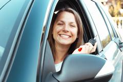 smiling girl sitting in a car and showing key - stock photo