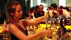 Beautiful blonde bartender pours beer Stock Footage