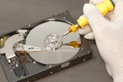 Hand with gloves repairs hard drive ,data recovery concept Stock Photos