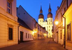 historical street in trnava with saint nicolas church slovakia - eastern euro - stock photo
