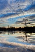 Electricity pylon with reflection in water at sunset Stock Photos