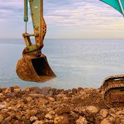 Excavating rocks by the sea Stock Photos