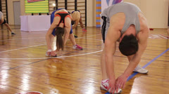 Hamstring stretch to right foot by group of people in gym. Stretching workout. Stock Footage