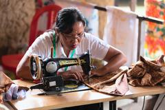 Balinese female tailor sew on a machine Stock Photos