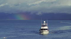 Motor Yacht with US Flags Oncoming with Rainbow and Clouds Stock Footage