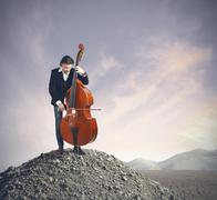 musician playing bass at the desert - stock photo