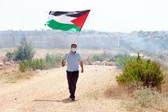 palestinian protester holding flag by wall of separation west bank - stock photo