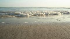 Waves on sandy sea foreshore - stock footage