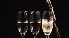 Endless stream of champagne into glasses in slow motion against black background Stock Footage