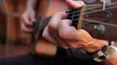 Acoustic guitarist playing chords, close-up moving from body up neck. - stock footage