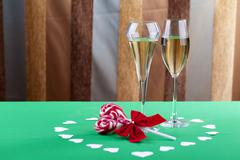 two glases of champagne next to a heart shape candy - stock photo