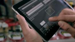 Seller forms a list items on the tablet - stock footage