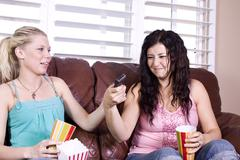 Two girls sitting on the sofa watching a movie Stock Photos