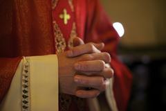 Catholic priest on altar praying during mass Stock Photos