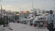 Cannes Pedestrians walk by the sea with huge sailing boats. Stock Footage