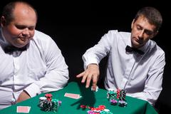 Two gentlemen in white shirts, playing cards Stock Photos