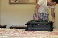 Young man unpacking his case in hotel Stock Footage