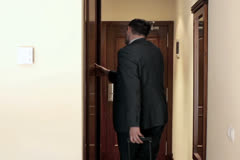 Young businessman with case leaving the hotel room Stock Footage