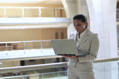 Smiling businesswoman with laptop in the office hall, steadycam shot Stock Footage