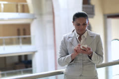 Young businesswoman with smartphone in the office hall, steadycam shot Stock Footage