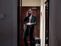 Young businessman talking on cellphone while getting into the hotel room Stock Footage