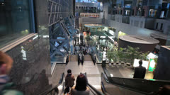Moving down on escalator with people. Kyoto railway station hall, Japan Stock Footage