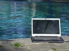 Modern laptop by the pool, super slow motion, shot at 240fps NTSC Stock Footage