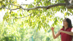 Brunette Young Adult Woman Hangs on Tree Branch - stock footage