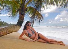 Young woman in bikini laying under palm tree Stock Photos
