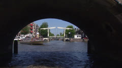 Amsterdam cruise canal district under stone bridge + cyclist crossing Stock Footage