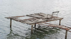 Lonely bench on broken pontoon on the lake Stock Footage