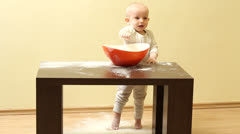 Cute little baby taking off the flour from the bowl and throwing off the floor - stock footage
