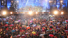Crowd at concert under the rain - stock footage