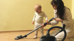 Mother showing to baby how to make clean with vacuum cleaner  Stock Footage