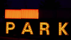 Flashing Neon Sign in City Park Stock Footage
