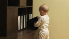 Active baby boy trying to arrange the books in a bookcase and give up - stock footage