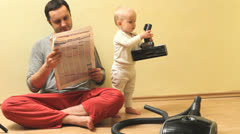 Father read the newspaper while baby searching the aspirator Stock Footage
