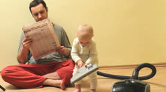 Baby cleaning the house with aspirator while father read the newspaper Stock Footage