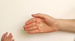 Little baby hand take a sea star from mother hand Stock Footage