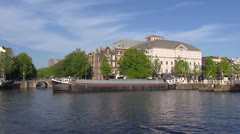 AMSTERDAM -  River Amstel with barge boat sailing in front of city theater Stock Footage