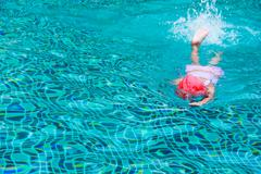 Kid swimming on a blue water pool Stock Photos
