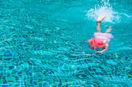 Stock Photo of kid swimming on a blue water pool