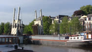 Stock Video Footage of AMSTERDAM -River boat passes open draw bridge crossing river Amstel
