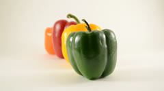 Green, Yellow, Red and Orange Peppers Against White - Dolly Right Stock Footage