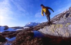 young man in yellow jacket hiking in rocky terrain with mountain view - stock photo